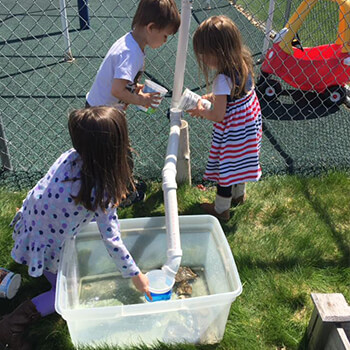 Kids playing with water experiment at Toddle Inn