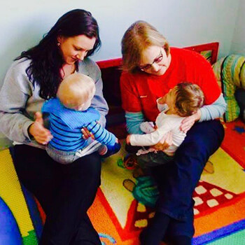 Teachers playing with infants at Toddle Inn
